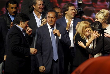 Argentina's ruling party candidate Daniel Scioli next to his vice-presidential candidate Carlos Zannini (L) greets supporters after elections in Buenos Aires