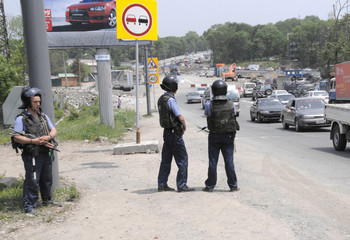 Police stand at a road to Russia's far eastern city of Vladivostok