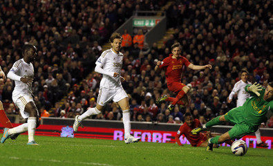 Swansea's Dyer scores past Liverpool's Jones during their English League Cup soccer match at Anfield in Liverpool