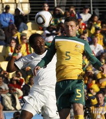 Ghana's Asamoah Gyan challenges Australia's Jason Culina for the ball during their 2010 World Cup Group D soccer match at Royal Bafokeng stadium in Rustenburg