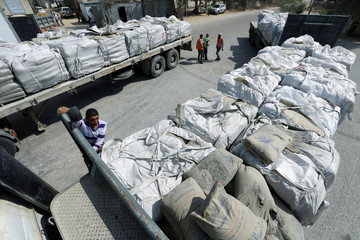 A Palestinian stands on a truck loaded with bags of cement at the Kerem Shalom crossing between Israel and southern Gaza Strip
