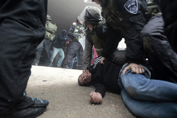 Israeli police and border police officers detain a Palestinian protester during clashes in Shuafat refugee camp