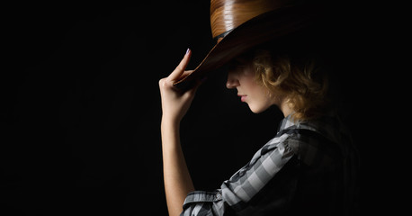 Beautiful girl in a cowboy's hat isolated on black background .