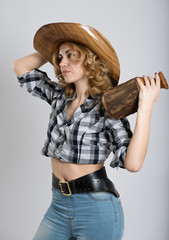 Beautiful girl in a cowboy's hat holding wooden bottle ..