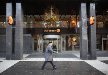 A man walks past Swedbank head office in Stockholm