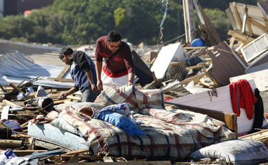 People search for salvageable items among the destruction left by a major earthquake and ensuing tsunami in Llolleo