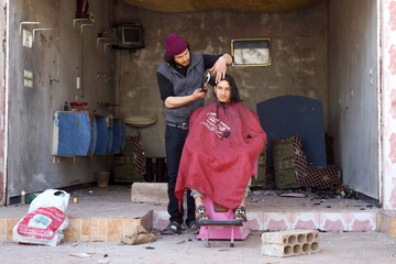 A barber cuts the hair of a customer outside his damaged salon in the rebel held al-Ghariyah al-Gharbiyah town, in Deraa province