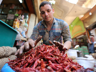 A worker at an outdoor market selling herbs and spices in Cairo