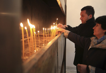 Local Kosovo Serbs light candles while praying in a church during Orthodox Christmas celebrations, in Partes