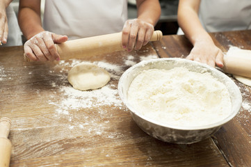 Making pastries from dough with stuffing. Children's hands close-up.