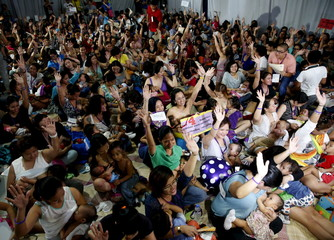 Mothers raise their hands as they breastfeed their children in Mandaluyong