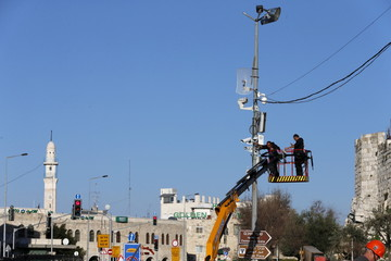 Workers install security cameras on a street pole near Damascus Gate in Jerusalem's Old City