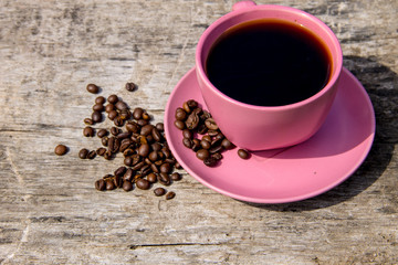Pink cup of coffee and coffee beans on rustic wooden table