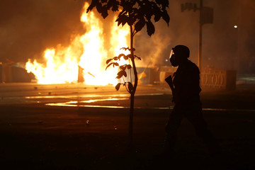 A riot policeman clashing with anti-government demonstrators, is pictured next to burning barricades during a protest against a constitutional amendment, known as PEC 55, that limit public spending, in front of Brazil's National Congress in Brasilia