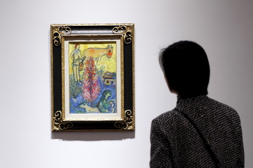 """Woman looks at Marc Chagall's """"Le buisson rose"""" during a media preview of Christie's Shanghai Spring Auction in Shanghai"""