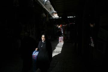 A nun walks through a market in Jerusalem's Old City