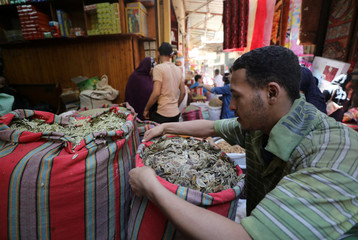 A worker sells herbs and spices at an outdoor market in Cairo