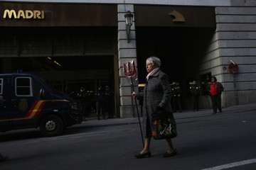 Woman carrying a trident walks past the headquarters of Spanish nationalised lender Bankia in Madrid