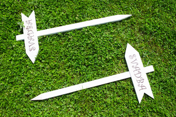 """""""Svadba""""  (slovak """"Wedding"""") words on the white wooden arrows, lying on the green grass"""