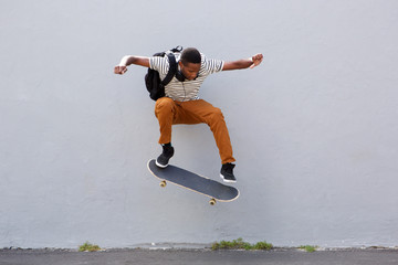 Full body young male skateboarder doing a trick outdoors