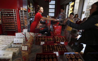 A salesperson sells caneles, a small French pastry, at the Maison Baillardran cake shop in Bordeaux