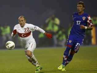 Balci of Turkey challenges Mandzukic of Croatia during their Euro 2012 playoff qualifying soccer match at Maksimir stadium in Zagreb