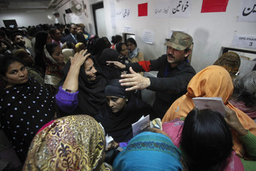A hospital staff asks women to line up who gathered to receive free medication from a pharmacy at the Punjab Institute of Cardiology (PIC) in Lahore