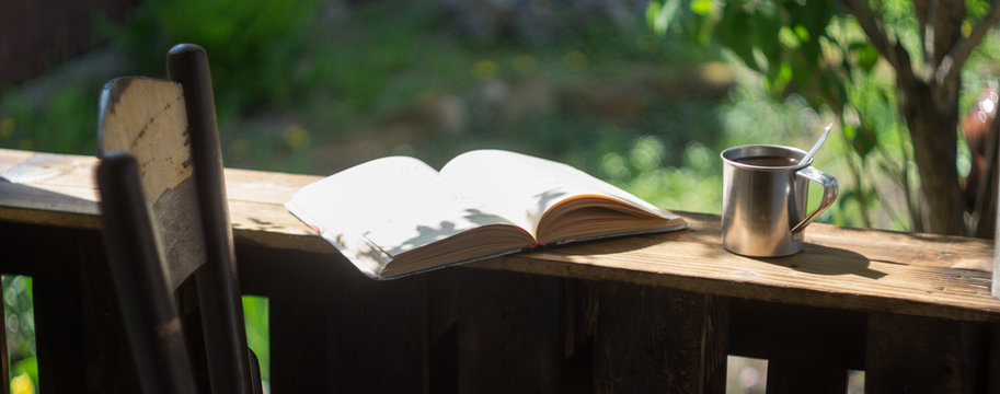Metal mug, book and chair on a wooden terrace