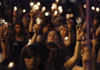 Uruguayan women wearing black dresses and veils hold candles as they demonstrate against domestic violence along 18 de Julio street in Montevideo