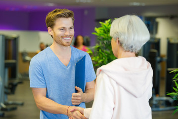 man with clipboard greeting woman at fitness center