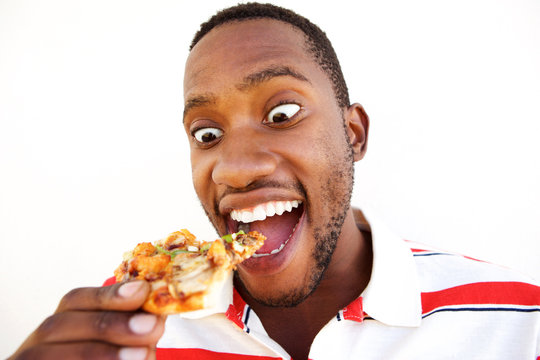 Excited young african man eating pizza