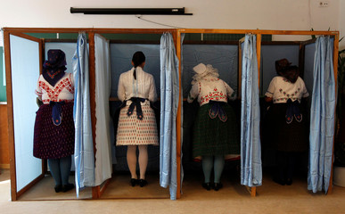 Hungarian women wearing traditional costum fill their ballot papers at a polling station during a referendum on EU migrant quotas in Veresegyhaz