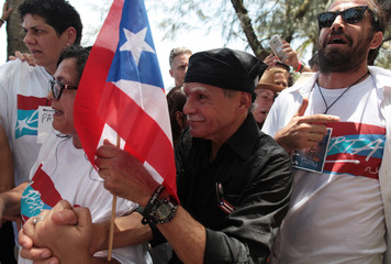 Puerto Rican Oscar Lopez Rivera carries a national flag as he meets with supporters after being released from house arrest in San Juan