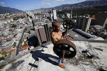 "Rivas lifts weights on a balcony on the 28th floor of the ""Tower of David"" skyscraper in Caracas"