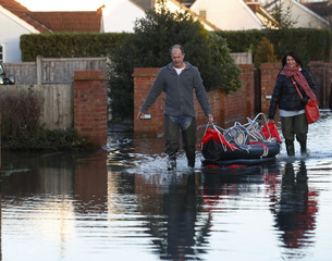 Residents bring back stools in a canoe to raise their furniture higher after the river Thames flooded the village of Wraysbury, southern England