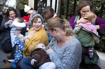 Demonstrators feed their babies during a protest in support of breastfeeding in public, outside Claridge's hotel in London