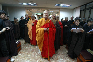 Sik, a prominent Buddhist leader in Hong Kong, pray along with other Buddhist devotees during a service in Hong Kong