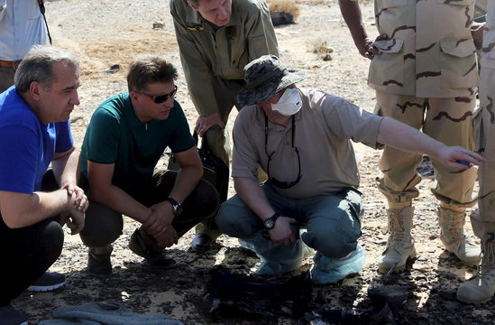 Puchkov, Russian Minister for Emergency situations and Russian Transport Minister Sokolov listen to a military investigator at the crash site of a Russian airliner in the al-Hasanah area in El Arish city, north Egypt