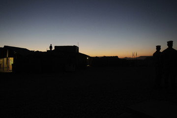 A U.S. Marine of Fox Co, of 2nd Battalion, 7th Marines Regiment, is silhouetted while standing guard on a roof during a ceremony of the 275th U.S. Marines Corps anniversary at Combat Outpost Muza Qal-Ah in Helmand province