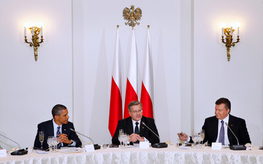 U.S. President Obama and Ukrainian President Yanukovych listen as Polish President Komorowski speaks during an official dinner in the Presidential Palace in Warsaw