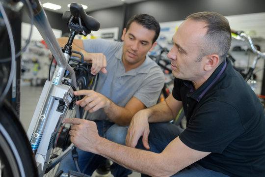 mechanic repairing battery powered bicycle in his workshop