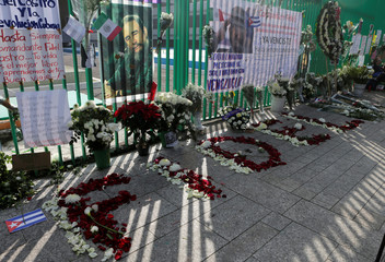 Pictures of Castro are seen beside his name made with flowers during a tribute ceremony outside the Cuban Embassy in Mexico City