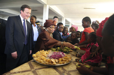 Britain's PM Cameron and Liberian President Sirleaf visit a market in Monrovia