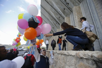 Demonstrators prepare to release balloons during a demonstration by Palestinian and Israeli activists calling for a better future for both people and ahead of the annual International Women's Day, near a section of the Israeli barrier in Bethlehem