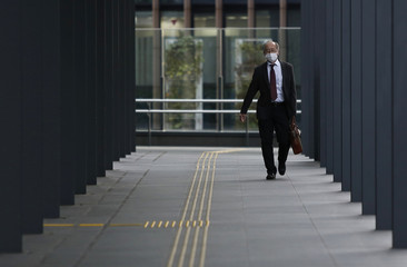 A man walks past a corridor at a business district in Tokyo