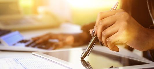 Banner Dunkelhäutige Frau kalkuliert mit Stift auf Tablet im Gegenlichtt