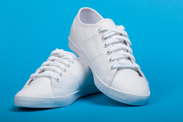 Pair of new white sneakers on blue background