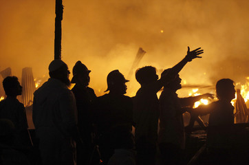 Firemen and members of the public look at a fire in a slum in Mumbai