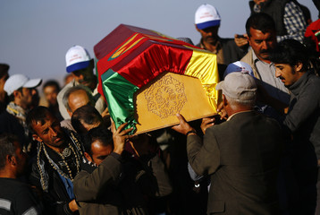 Turkish Kurds carry a coffin during the funeral of three Kurdish fighters killed during clashes against Islamic State in Syrian town of Kobani, at a cemetery in the southeastern town of Suruc