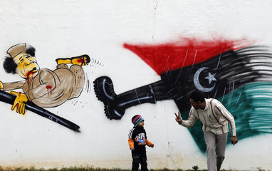 A man plays with his son in front of a cartoon depicting Libyan leader Muammar Gaddafi in Benghazi